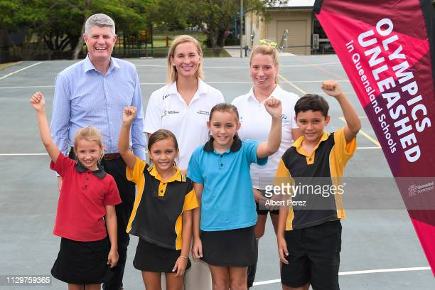 Minister for Local Government Stirling Hinchliffe and olympic athletes Maddie Groves and Monique Murphy pose for photographs with students during a...