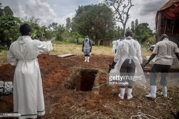 Minister leads a final prayer, as the burial of a coronavirus victim is carried out by the district health team in Gulu, northern Uganda. The East...