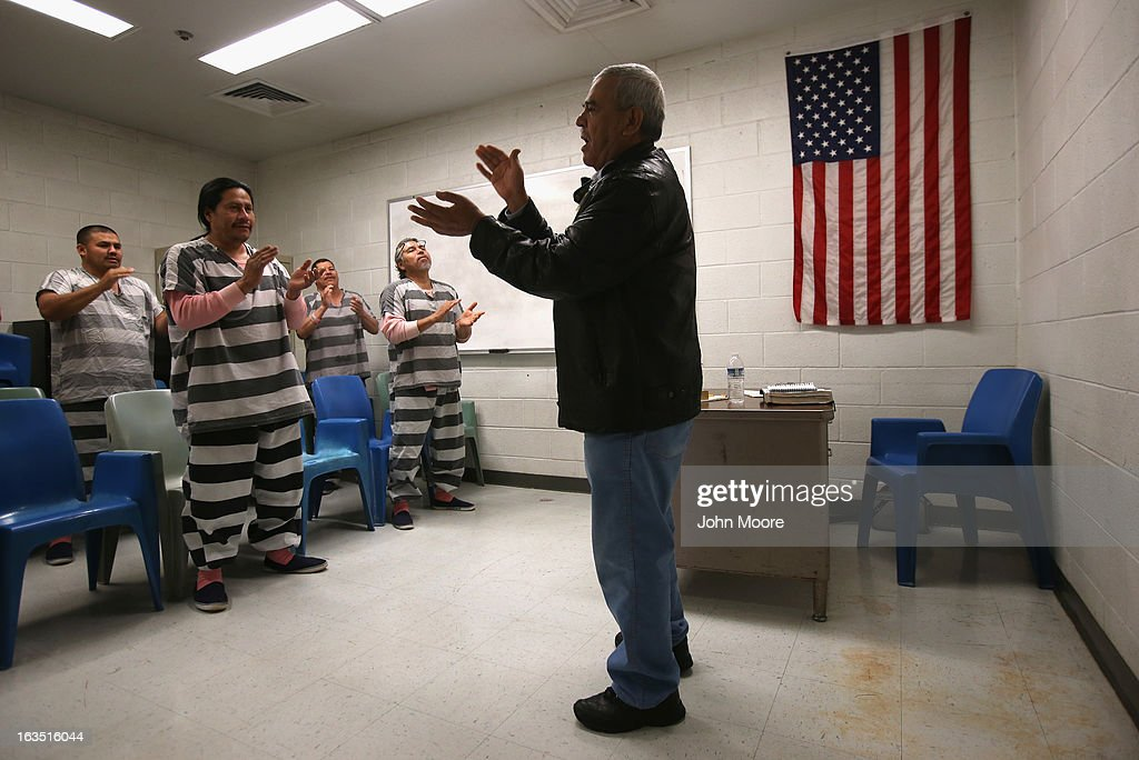 A minister leads immigrant inmates during a Protestant church service at the Maricopa County Tent City jail on March 11, 2013 in Phoenix, Arizona. Striped uniforms and pink undergarments are standard issue at the facility. The tent jail, run by Maricopa County Sheriff Joe Arpaio, houses undocumented immigrants who are serving up to one year after being convicted of crime in the county. Although many of immigrants have lived in the U.S for years, often with families, most will be deported to Mexico after serving their sentences.