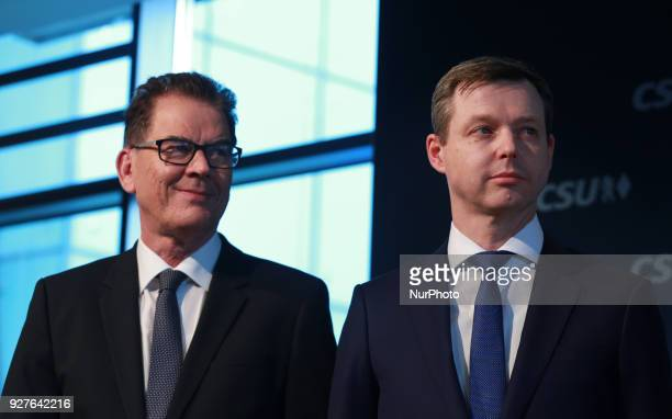 Minister of economic relations and development Gerd Müller and designated state secretary of defense stand on the stage in Munich Germany on 5 March...