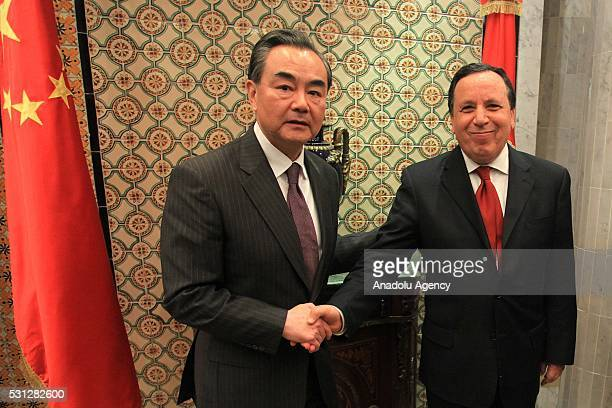 Minister of Foreign Affairs of China Wang Yi and Tunisian Foreign Minister Khamis alJehinawi shake each others' hands before their meeting in Tunis...