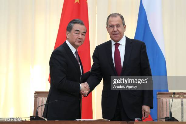 Minister of Foreign Affairs of Russia, Sergey Lavrov and Chinese State Councillor and Foreign Minister, Wang Yi shake hands as they pose for a photo...