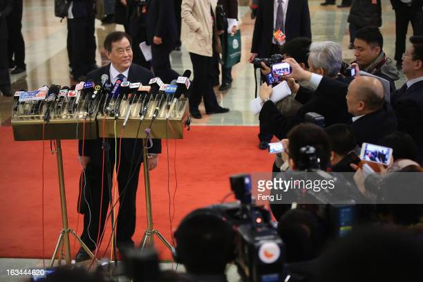 Minister of Railways Shen Guangzu answer media questions as he arriving at the Great Hall of the People to attend a plenary session of the National...