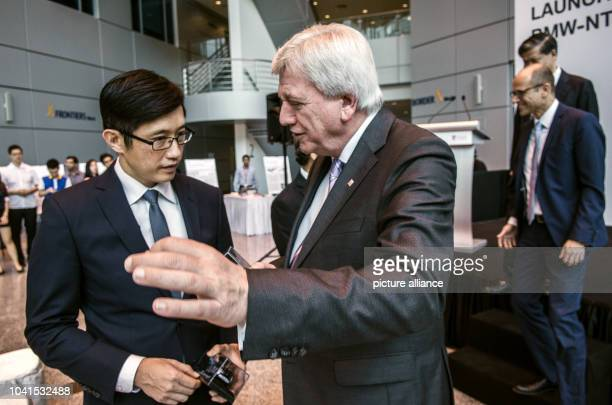 Minister of State at Singapore_s Ministry of Trade and Industry Teo Ser Luck speaks with Premier of the German Federal State of Hesse and President...