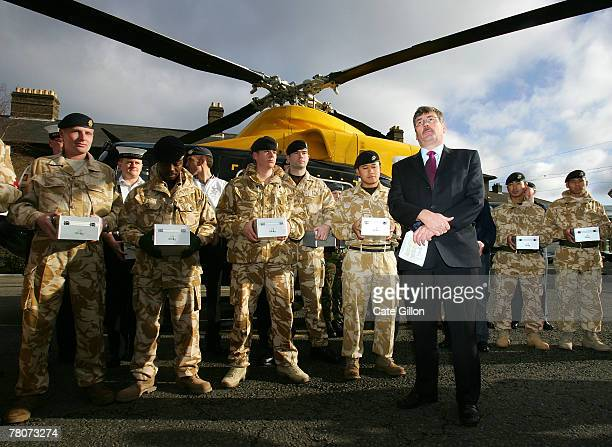 Minister of State for the Armed Forces , Bob Ainsworth with troops before they load Christmas gifts donated by charity UK4UThanks! onto a helicopter...