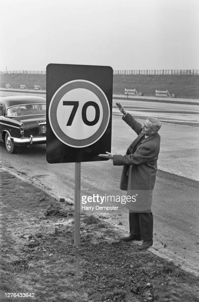 Minister of Transport Tom Fraser on the M4 motorway with a new speed limit sign for 70 miles per hour, UK, December 1965. The speed limit is being...