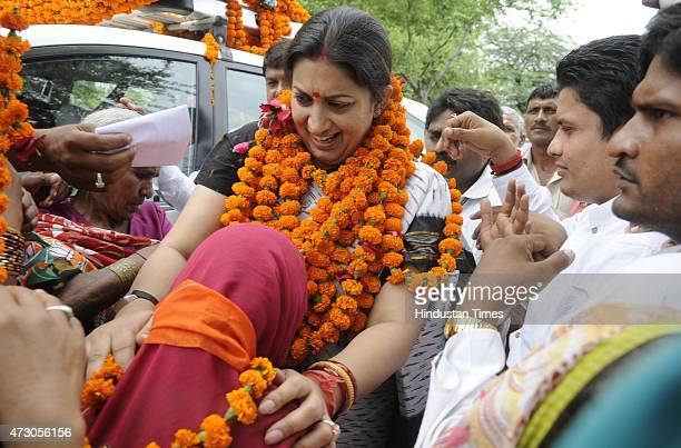 Minister Smriti Irani being welcomed by village women during her visit on May 12 2015 in Amethi India HRD Minister challenged the Congress Vice...