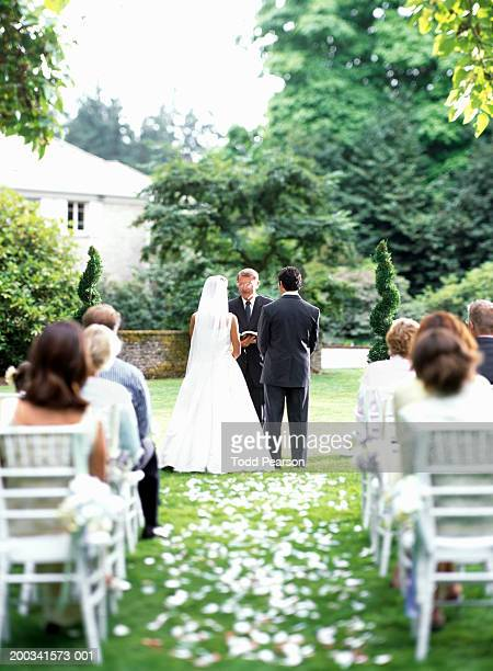 minister speaking to bride and groom during outdoor wedding ceremony - wedding vows stock pictures, royalty-free photos & images