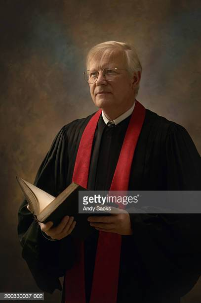 Minister wearing robe, holding bible