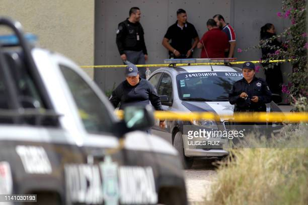 Ministerial agents are seen outside a safe house where eight people with signs of torture were found alive along with four dead ones, in Tlajomulco...