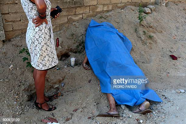 A ministerial officer stands next to the body of a woman murdered on December 11 2015 in Acapulco Guerrero state Mexico Guerrero is one of Mexico's...