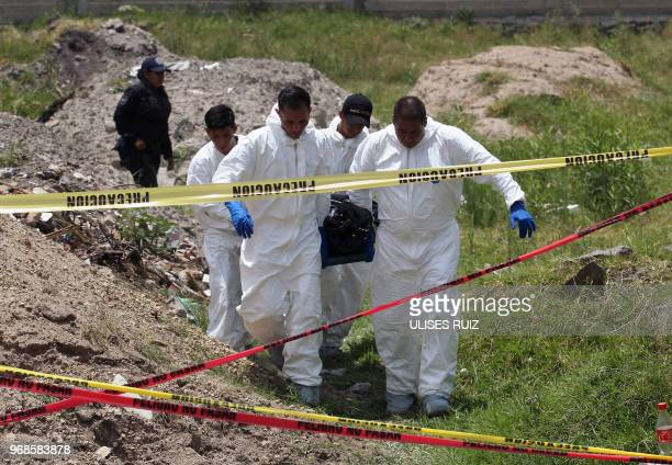 Ministerial police officers carry a body found in a clandestine common grave, at the Lomas del Aeropuerto neighborhood in El Salto municipality,...