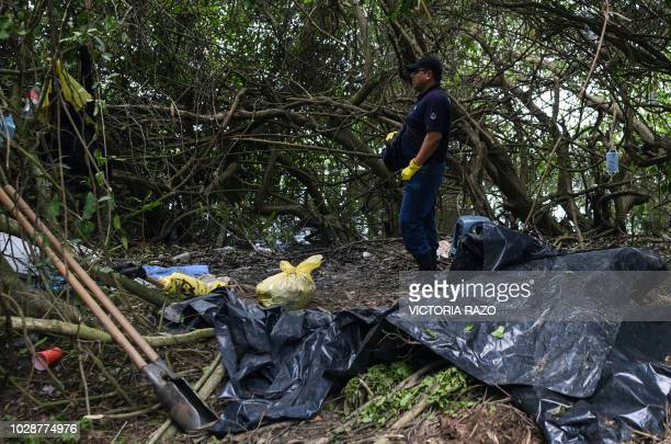 Ministerial police officers work at the site of a mass grave where at least 166 bodies were discovered since exhumations began on August 8 at...