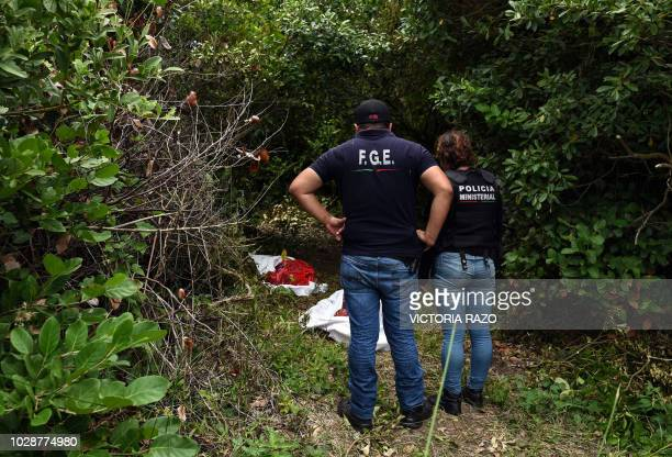 Ministerial police officers work at the site of a mass grave, where at least 166 bodies were discovered since exhumations began on August 8, at...