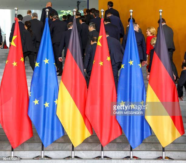 Ministers and delegation members leave behind the Chinese European and German flags after posing for a group photo with the German Chancellor and the...