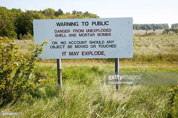 Ministry of Defense warning sign about the danger of unexploded shells and bombs on the firing ranges of Salisbury Plain Wiltshire England