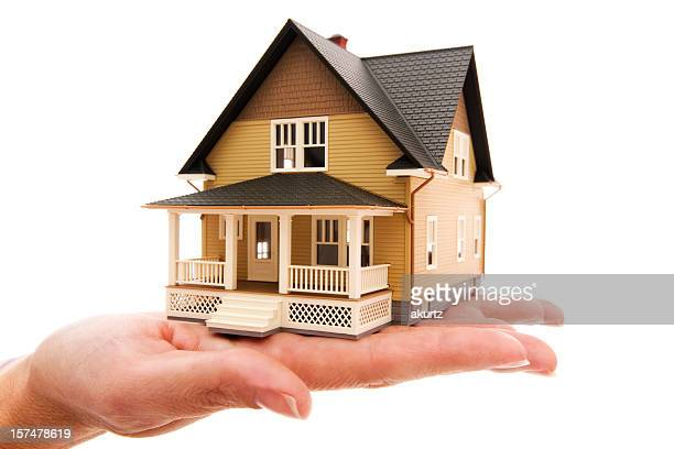 Miniture house model human hand displaying american dream isolated