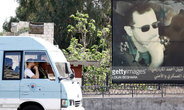A minivan drives past a portrait of Syrian President Bashar alAssad in Damascus on April 7 2017 US forces fired a barrage of cruise missiles at a...