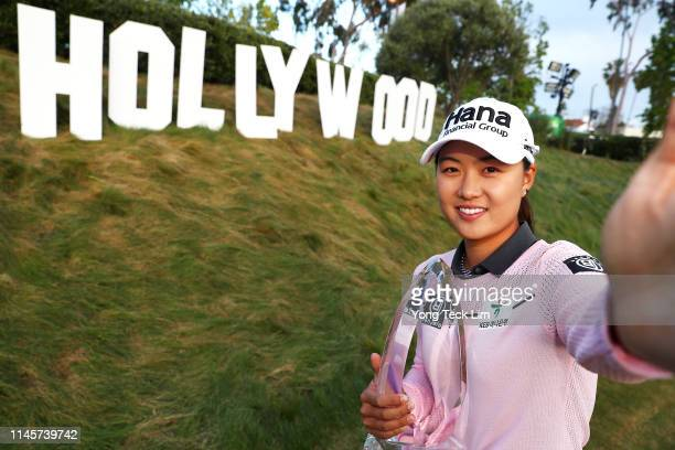 Minjee Lee of Australia imitates a selfie as she poses with the winner's trophy during the HUGELAIR PREMIA LA Open at Wilshire Country Club on April...