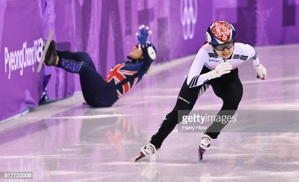 Minjeong Choi of Korea races past as Elise Christie of Great Britain crashes during the Ladies' 500m Short Track Speed Skating final on day four of...