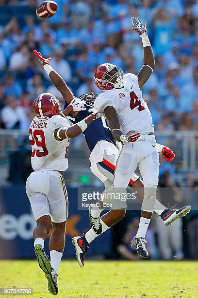 Minkah Fitzpatrick and Eddie Jackson of the Alabama Crimson Tide defend Markell Pack of the Mississippi Rebels as an overthrown pass goes out of his...