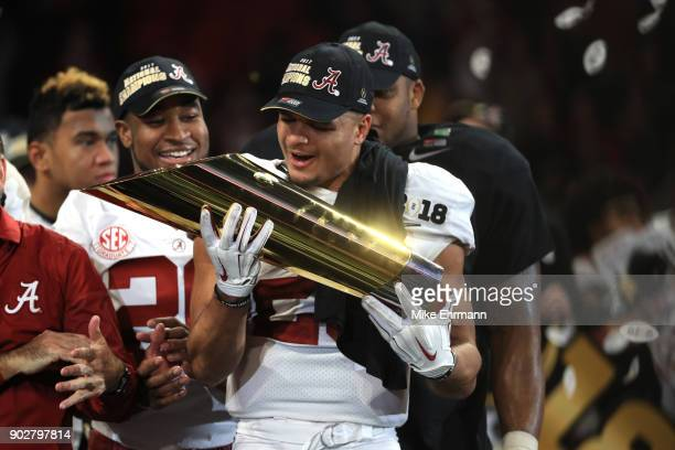 Minkah Fitzpatrick of the Alabama Crimson Tide holds the trophy while celebrating with his team after defeating the Georgia Bulldogs in overtime to...