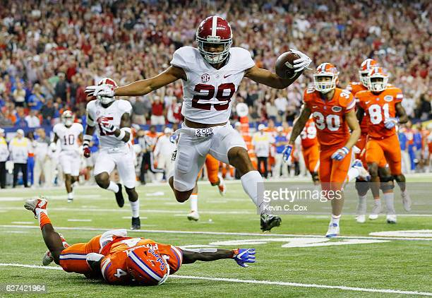 Minkah Fitzpatrick of the Alabama Crimson Tide returns an interception for a touchdown as Brandon Powell of the Florida Gators defends in the first...