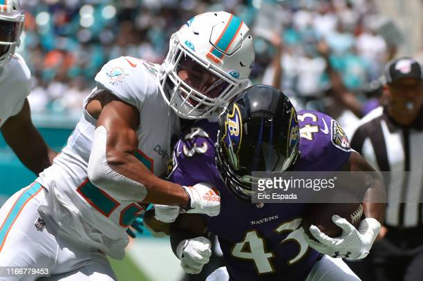 Minkah Fitzpatrick of the Miami Dolphins knocks Justice Hill of the Baltimore Ravens out of bounds during the first quarter of the game at Hard Rock...
