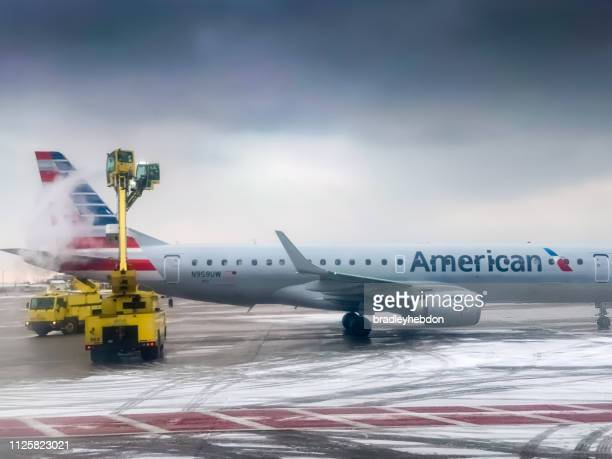 Minneapolis airport ground staff de-ice the wings of American Airlines aircraft