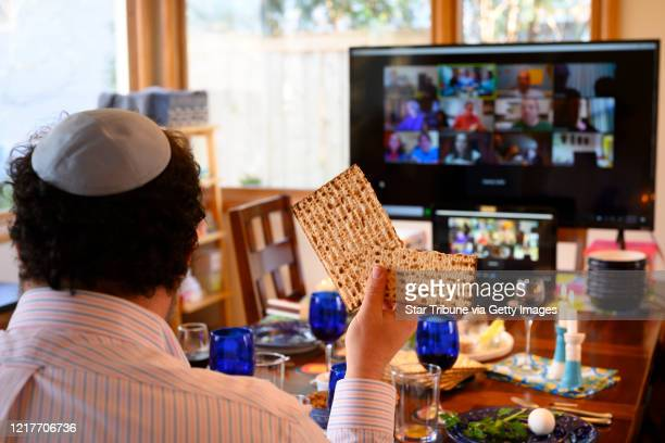 Bruce Manning held up matzo which he just broke in half as part of Passover seder ritual as he took part in a virtual seder alongside his family...