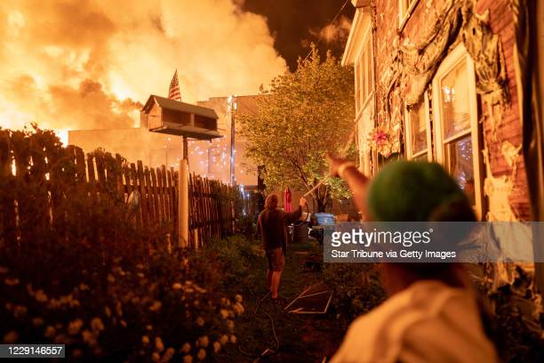 Neighbors fought with garden hoses and buckets to save homes after rioters set fire to a multistory affordable housing complex under construction...