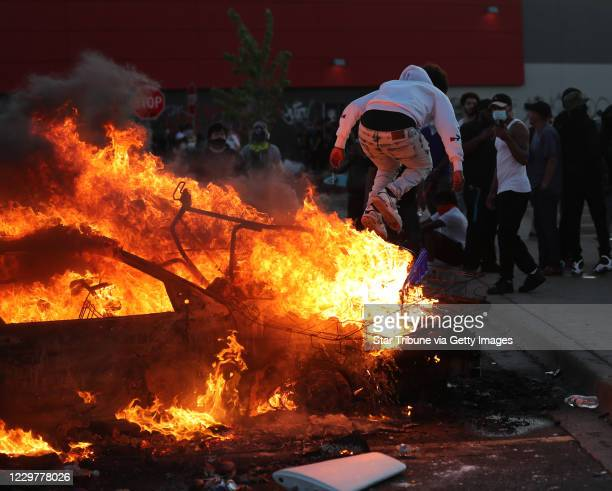 A man jumps off of a burning car in the Target Parking lot on E Lake St during a third night of unrest following the death of George Floyd while in...