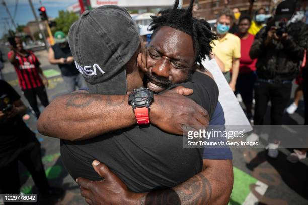 Former Minnesota Gopher and NFL player Tyrone Carter pleaded with protesters not to tear up their city as he hugged Tony L Clark at the site where...