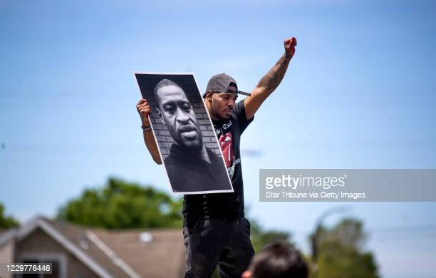 Tony L Clark held a photo of George Floyd were he was killed in front of the Cup Food Store Protesters gathered at 38th and Chicago where George...