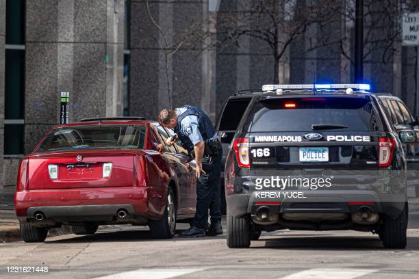 Minneapolis Police officer checks a suspicious car without a plate parked near the Hennepin County Government Center as the jury selection begins at...