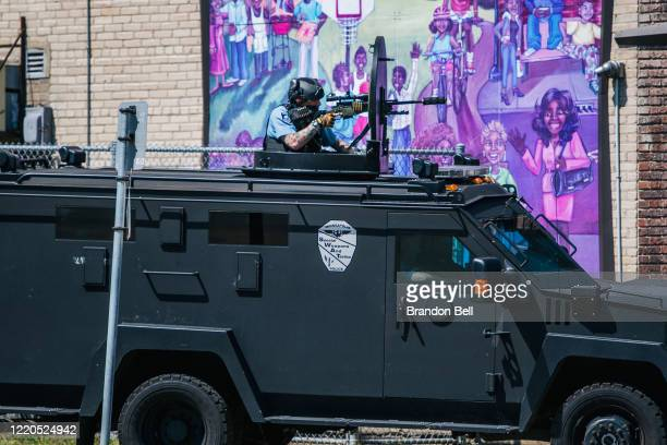 Minneapolis Police officers sit in an armored vehicle with guns drawn at a crime scene on June 16 2020 in Minneapolis Minnesota The Minneapolis...