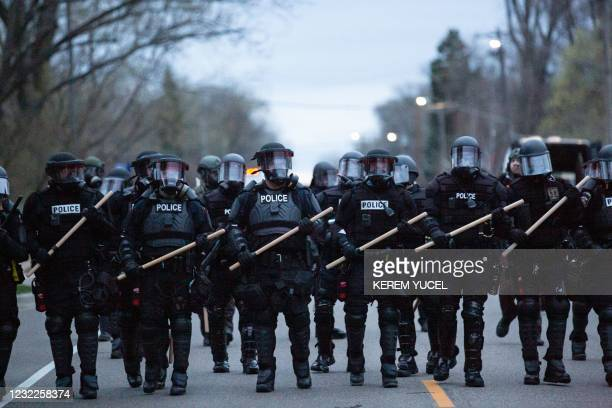 Minneapolis police officers stand in line as they are confronted by protesters after an officer shot and killed a black man in Brooklyn Center,...