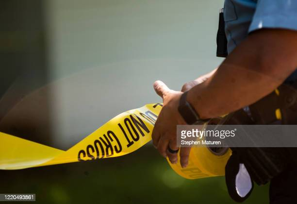 Minneapolis Police officers unrolls caution tape at a crime scene on June 16, 2020 in Minneapolis, Minnesota. The Minneapolis Police Department has...