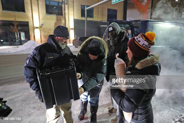 Minneapolis Police Sgt Grant Snyder and Pastor John Steger hand out gloves hats and food to the homeless while temperatures dropped to 24 degrees...