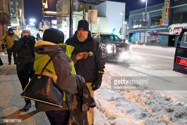 Minneapolis Police Sgt Grant Snyder hands out gloves hats and food to the homeless while temperatures dropped to 24 degrees Fahrenheit on January 30...