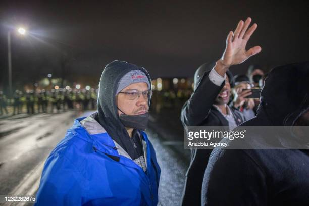 Minnesota Attorney General, Keith Ellison stands on the street near protesters as Brooklyn Center Mayor, Mike Elliott talks to protesters as protests...