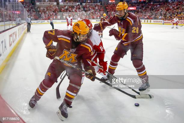 Minnesota forward Tommy Novak and Wisconsin center Tarek Baker battle for control of the puck while Minnesota defense Sam Rossini looks on during a...