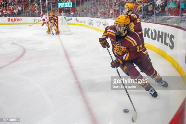 Minnesota forward Tommy Novak brings the puck out of the corner during a college hockey match between the University of Wisconsin Badgers and the...