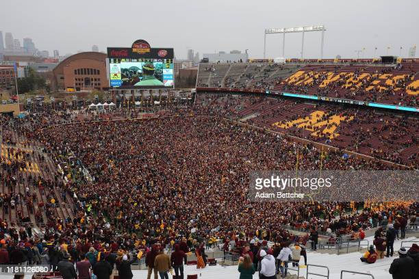 Minnesota Golden Gophers and fans storm the field while hoisting the Governor's Victory Bell after defeating the Penn State Nittany Lions 31-26 to...