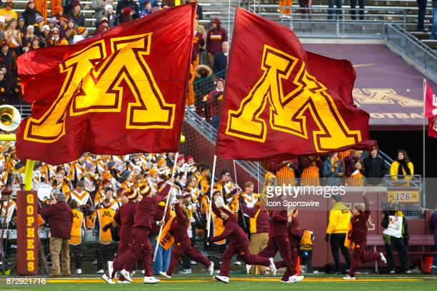 Minnesota Golden Gophers cheerleaders run with Minnesota flags during the Big Ten Conference game between the Nebraska Cornhuskers and the Minnesota...