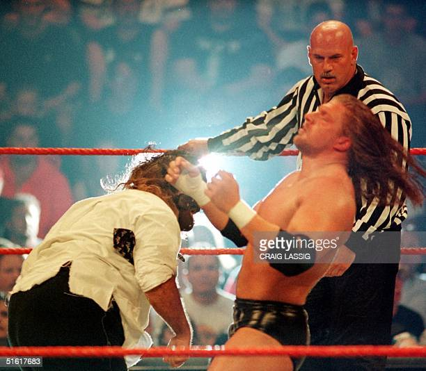 Minnesota Governor and former professional wrestler Jesse Ventura watches over the action as a guest referee during the World Wrestling Federation...
