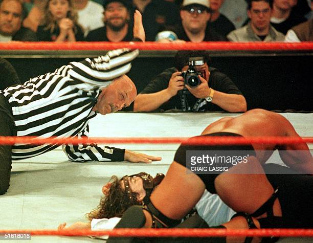 Minnesota Governor former professional wrestler and guest referee Jesse Ventura administers the three count as wrestler Stone Cold tries...