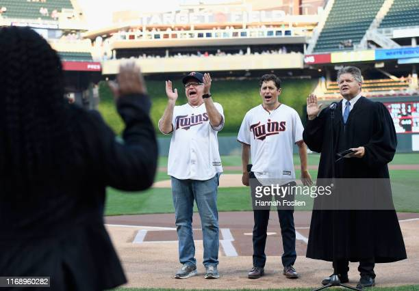 Minnesota Governor Tim Walz and Minneapolis Mayor Jacob Frey celebrate as a judge swears in a new group of American citizens before the game between...