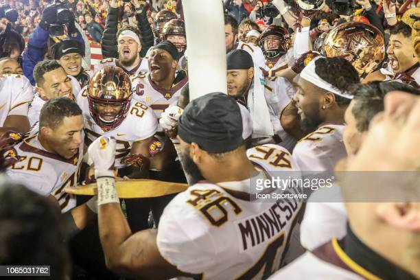 Minnesota linebacker Julian Huff tries to chop down the goal post with the Paul Bunyan axe following a win over Wisconsin in a college football game...