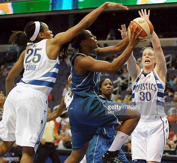Minnesota Lynx guard Monica Wright, center, drives for a shot between Washington Mystics defenders Monique Currie and Katie Smith during the first...